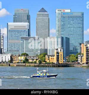Metropolitan police River Thames patrol passing modern landmark skyscraper building on Canary Wharf Isle of Dogs London Docklands skyline  England UK - Stock Image