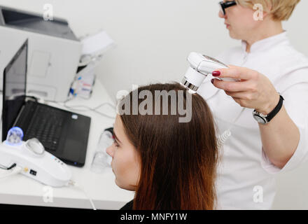 Doctor examines the hairy part of the patient's head - Stock Image