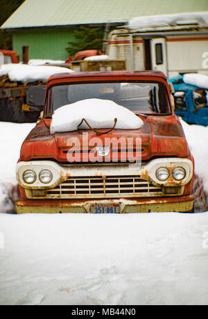 An old, red 1960 Ford F-100 pickup truck, in the snow, on the side of a barn, in Noxon, Montana.  This image was shot with an antique Petzval lens and - Stock Image