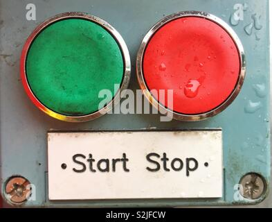 A red and a green button with a sign saying stop or start in a decision-making image about choice - Stock Image