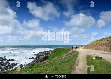 People walking along the coastal path on the Headland in Newquay in Cornwall. - Stock Image