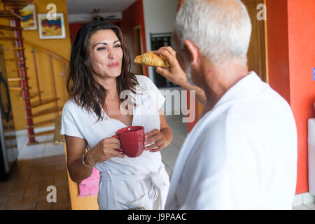 Breakfast of unequal couple - older man feeding a croissant to younger woman, Nuevo Vallarta, Nayarit, Mexico - Stock Image