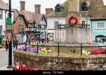 War memorial with flowers and red poppy wreaths in the old High Street, Arundel, West Sussex, England, UK, Britain - Stock Image