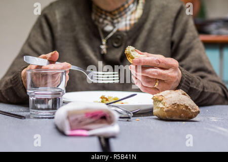 Elderly person eating. - Stock Image