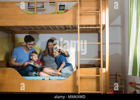 Father and the pregnant mother reading a book to their two sons on bunkbed, Munich, Germany - Stock Image