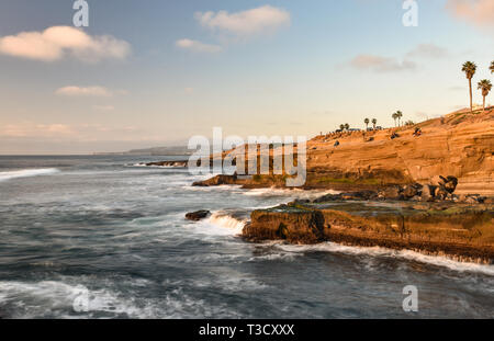 Waves from Pacific Ocean crashing on rocky shoreline along famous Sunset Cliffs Natural Park, Point Loma, San Diego, CA, USA - Stock Image