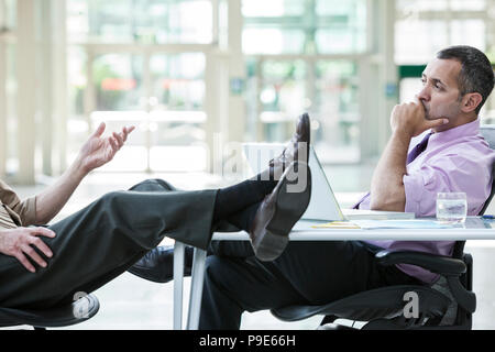 Two businessmen talking at a desk with one person's feet resting on top of the table - Stock Image