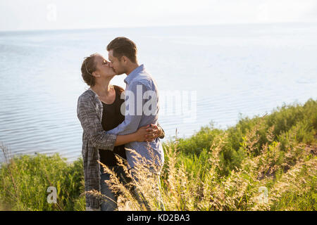Man and woman kissing by sea - Stock Image