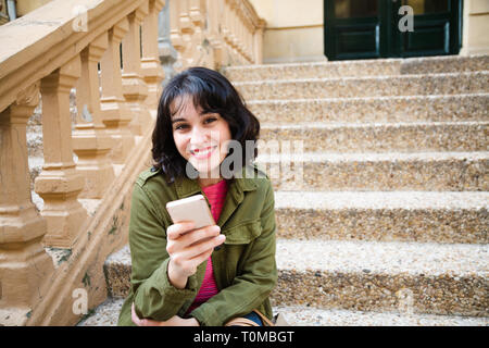 Happy young beautiful woman in green jacket using her smart phone sitting on stairs outdoors - Stock Image