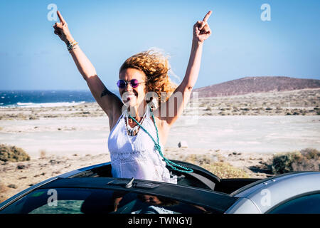 Travel and happiness with convertible car for curly happy cheerful people adult woman celebrating the alternative vacation trip - ocean and tropical s - Stock Image