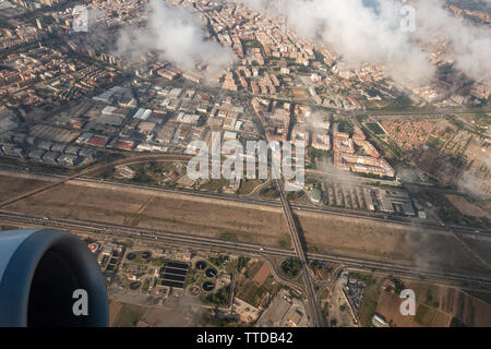 view showing the jet engine of a ryanair passenger Boeing 737 jet flying above the clouds with city below - Stock Image