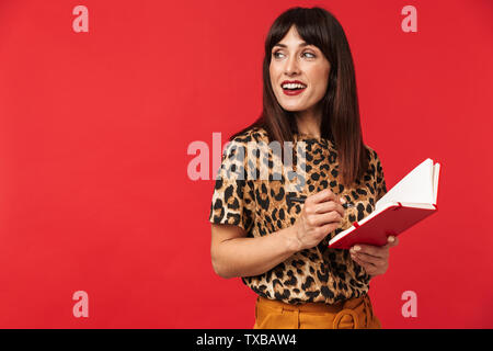Image of a beautiful young woman dressed in animal printed shirt posing isolated over red background writing notes in notebook. - Stock Image