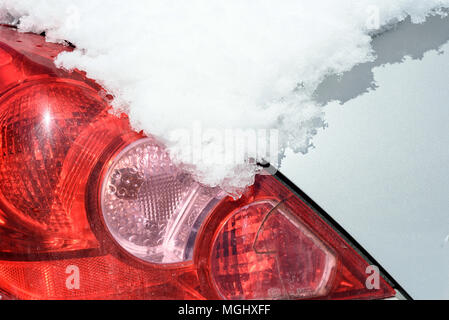Car rear view light and indicator covered and obscured in a thick blanket of winter snow. Copy space area for extreme weather travel and transport con - Stock Image