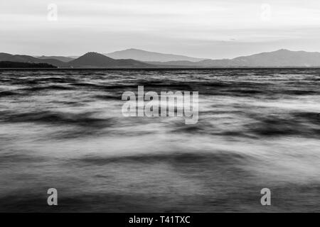 Close view of moving waves on a lake at dusk. - Stock Image