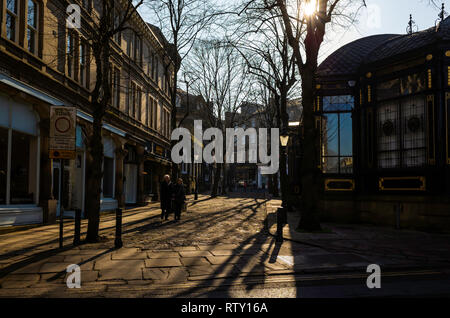 A middle aged couple with shopping bags walking in Crown Place in the centre of historic Harrogate in morning early spring sunshine - Stock Image