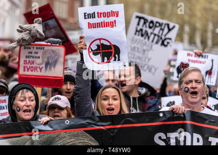 Protesters at a stop trophy hunting and ivory trade protest rally, London, UK. Female, females, women with placards. People - Stock Image