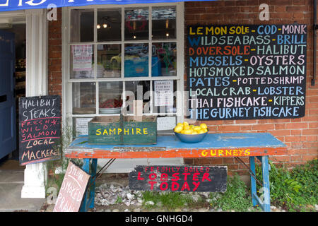 fish shop signs on front of Gueneys Fish shop in upmarket Norfolk village of Burnham Market - Stock Image