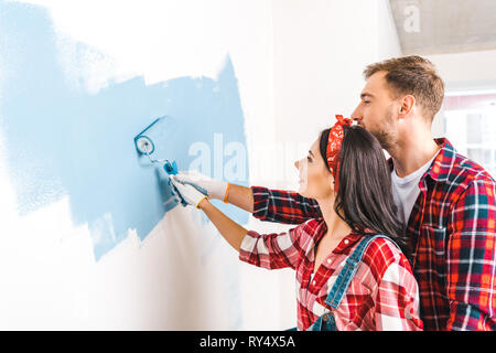 cheerful man and woman painting wall in blue color at home - Stock Image