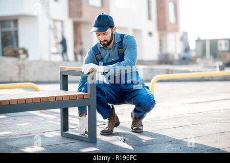 Handsome workman in uniform mounting a new bench on the playground outdoors - Stock Image