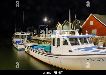 French River harbour, buildings, equipment and boats, photographed at night. - Stock Image