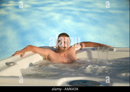 A man in a hot tub - Stock Image