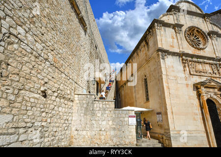 Tourists climb the staircase to the ancient city walls of Dubrovnik near Saint Saviour Church on the Dalmation coast of Croatia on a sunny summer day - Stock Image