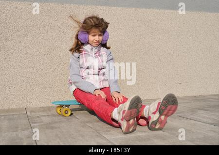 Little girl rides a skateboard, in area near the house, spring season, gray wall background. - Stock Image
