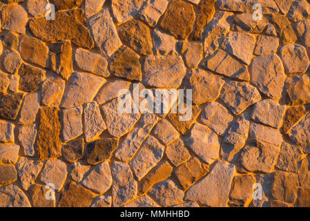 Close up view of a stone wall illuminated by late afternoon sunlight - Stock Image