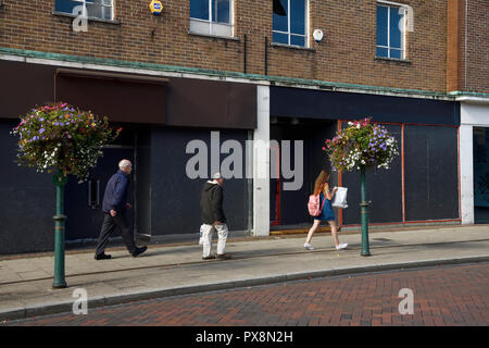 People walk past empty boarded up shops on Queensway in Crewe town centre UK - Stock Image