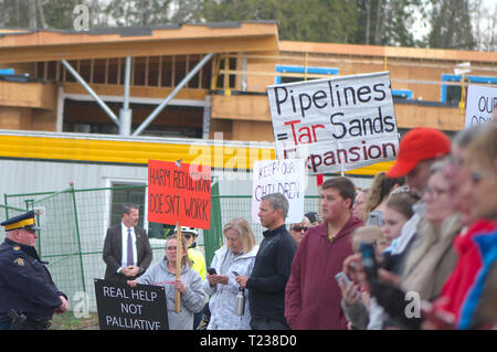 Protesters holding up signs at a media event in Maple Ridge, B. C. - Stock Image