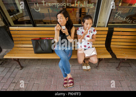 Mother and daughter eating gelato on  Rue Saint-Jean during a summer day in old Québec City in the Saint-Jean-Baptiste area of old Québec City, Canada - Stock Image