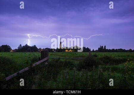 Lightning storm strikes near a small village at in in farmland, Zoeterwoude Zuidbuurt, the Netherlands - Stock Image