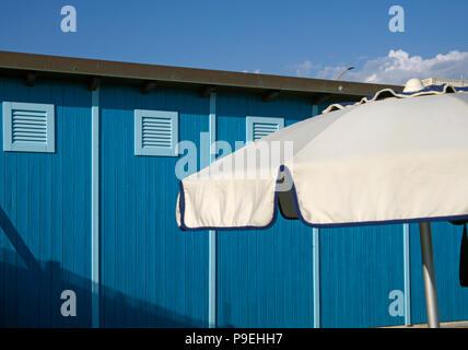 beach huts and parasol - Stock Image