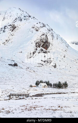 a white cottage in the mountains with snow in winter - Stock Image