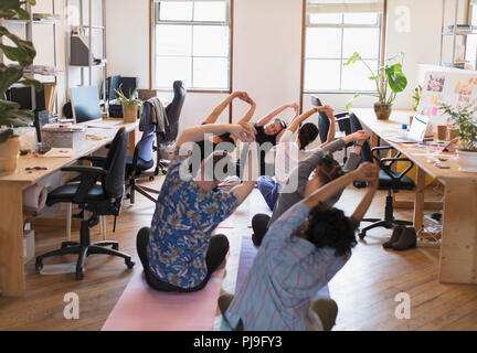 Creative business people stretching, practicing yoga in office - Stock Image