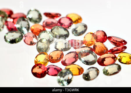 Small Natural Sapphires of different colours - red, yellow, orange and green - Stock Image
