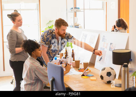 Creative designers reviewing story board proofs in office - Stock Image