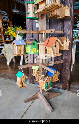 Colorful wooden handmade bird houses for sale at the Sweet Creek country roadside market in Pike Road Alabama, USA. - Stock Image