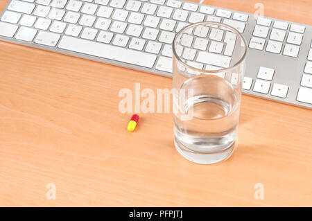 Glass of water and pill next to computer keyboard on desk - Stock Image