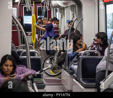 Passengers inside the carriage of a light rail carriage of an MTS 'Trolley' in San Diego, California, USA. - Stock Image