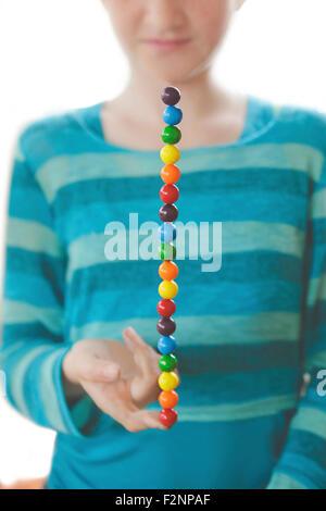 Caucasian girl balancing rainbow candies on finger - Stock Image