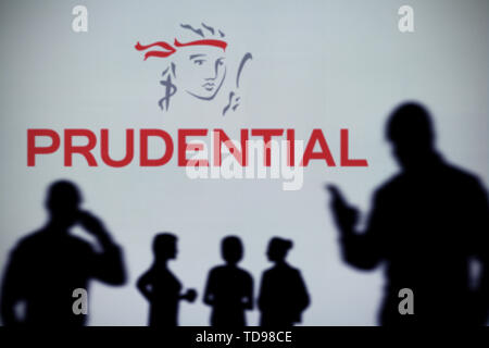 The Prudential Insurance logo is seen on an LED screen in the background while a silhouetted person uses a smartphone (Editorial use only). - Stock Image