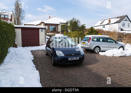 Cars parked on snow cleared drive in front of house - Stock Image