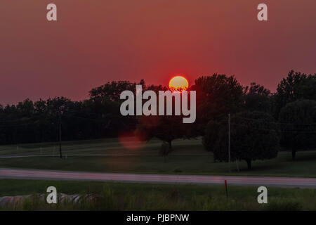 Orange ball of sun setting in the Oklahoma, USA countryside. Glowing, rosy and purple sky. - Stock Image