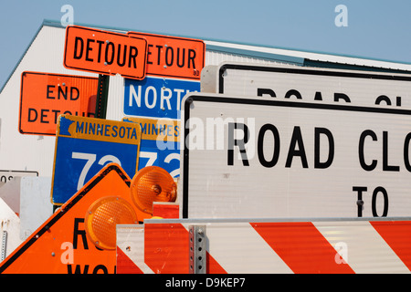 Construction road signs stacked up along the side of a street. - Stock Image
