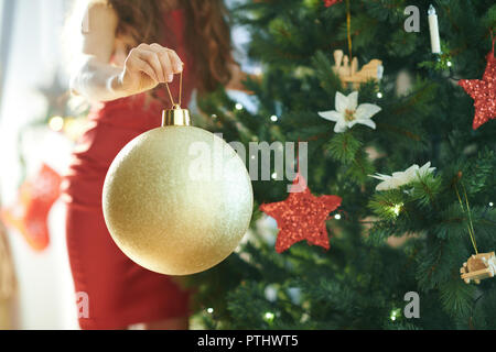 Closeup on stylish woman in red dress near Christmas tree hanging big gold Christmas ball - Stock Image