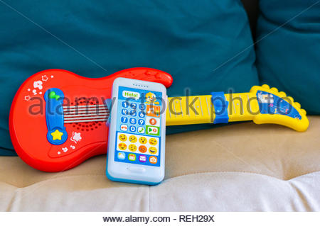 Poznan, Poland - October 10, 2018: Fisher Price toy telephone lying against a toy guitar on a sofa in soft focus - Stock Image