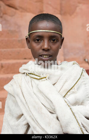 Young male pilgrim dressed in tradtional white robes, with a palm frond around his forehead, near the Bet Amanuel church, during the prayers on Ethiopia Easter Saturday, Lalibela, Ethiopia - Stock Image
