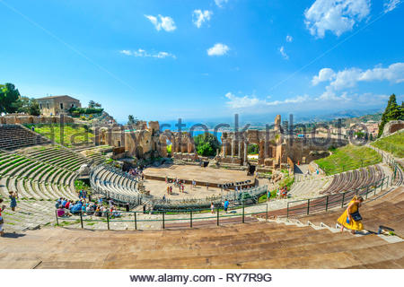 Visitors walk the ancient seating arena at the historic Greek Theatre on the Sicilian island of Taormina, Italy, with the sea, village and Mt Etna - Stock Image