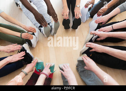 Active seniors stretching legs in circle - Stock Image